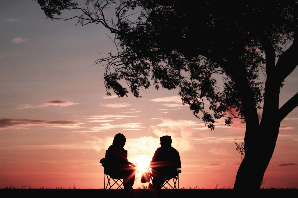 two people sitting in camp chairs under a tree watching the sunset